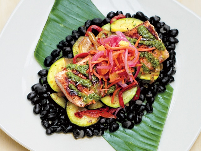 The chimichurri mahi mahi is pan-roasted; served on a bed of black beans, sautéed zucchini, red peppers, and onions; and topped with cilantro chimichurri sauce and a pickled carrot, onion, and orange salad.